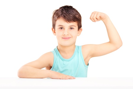 A child showing his muscles seated on a table isolated on white background photo