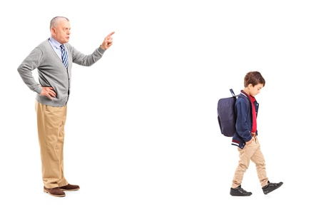 Full length portrait of a grandfather reprimanding a little boy, isolated on white background photo
