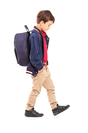 walking down: Full length portrait of a sad school boy walking, isolated on white background