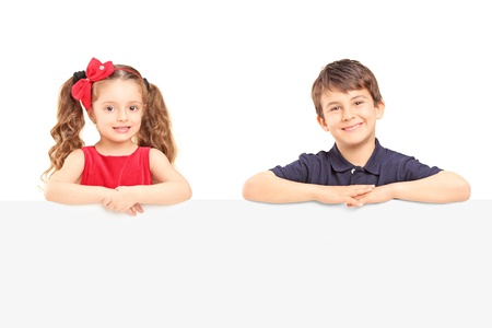 Little smiling boy and girl standing behind a blank panel isolated on white background Stock Photo - 19122429