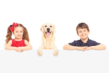 Smiling boy and girl standing behind a blank panel with a Labrador retriever dog isolated on white background