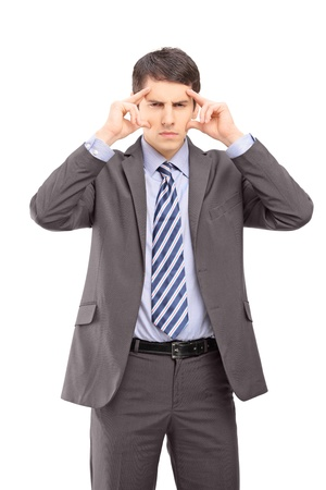 A young businessman holding his head in pain as a result of a headache isolated against white background photo