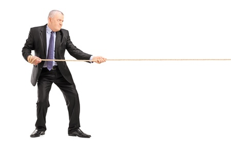 Full length portrait of a mature businessman in suit pulling a rope isolated on white background photo