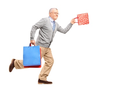 late 50s: Full length portrait of a mature gentleman running with shopping bags isolated on white background