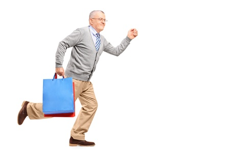 late 50s: Full length portrait of a smiling gentleman running with shopping bags isolated on white background