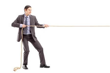 pulling rope: Full length portrait of a young businessman in suit pulling a rope isolated on white background