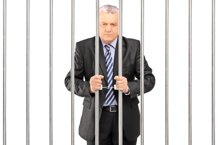people from behind: A handcuffed manager in suit posing in jail and holding bars, isolated on white background