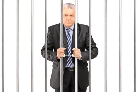 carcel: Un gerente esposado en traje posando en la c�rcel y la celebraci�n de barras, aislado sobre fondo blanco