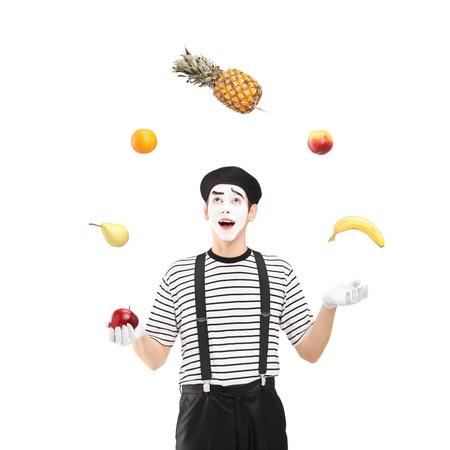 pantomima: Un sonriente mimo malabarismo frutas aisladas sobre fondo blanco Foto de archivo