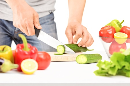Male cutting cucumber, preparing salad isolated on white background photo