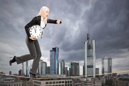 Full length portrait of a businesswoman running on a rope in the business center of Frankfurt, Germany photo