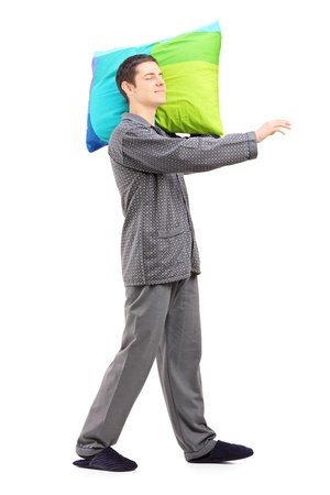 sleepwalker: Full length portrait of a man sleepwalking and holding a pillow, isolated on white background