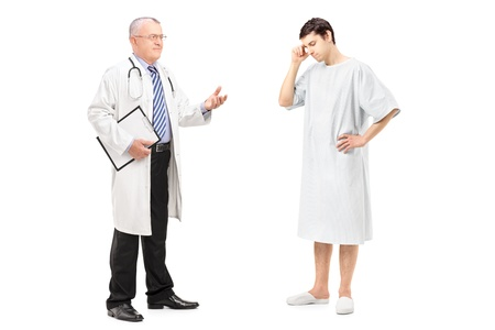 hospital gown: Full length portrait of a mature health specialist talking to a worried patient, isolated on white background