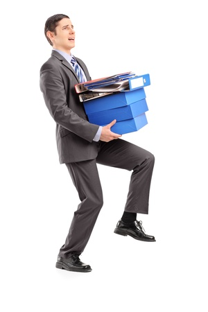 Full length portrait of a professional man carrying heavy folders, isolated on white background photo