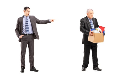 angry boss: Full length portrait of an angry boss firing an employee, isolated on white background