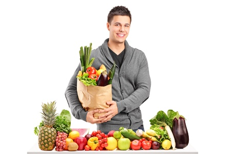 Handsome young man with a bag of groceries standing behind a pile of fruits and vegetables, isolated on white background photo