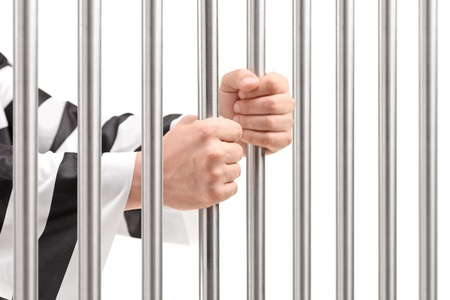 man in jail: Male hands holding prison bars Stock Photo