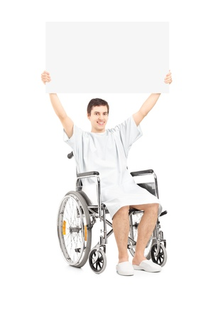 Male patient in a wheelchair holding a blank panel, isolated on white background photo