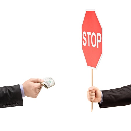 Man with a stop sign saying no to bribery, isolated on white background photo
