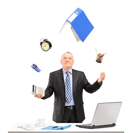 juggling: Mature businessman juggling in his office, isolated on white background