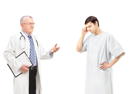Mature doctor talking to a worried male patient, isolated on white background photo