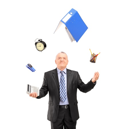 juggling: Mature man in a suit juggling with office supplies, isolated on white background Stock Photo