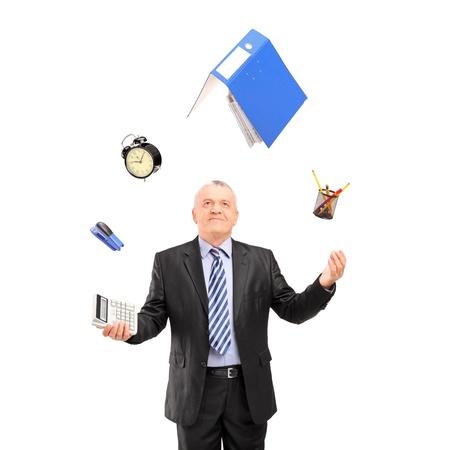Uomo maturo in un abito giocoleria con forniture per ufficio, isolato su sfondo bianco