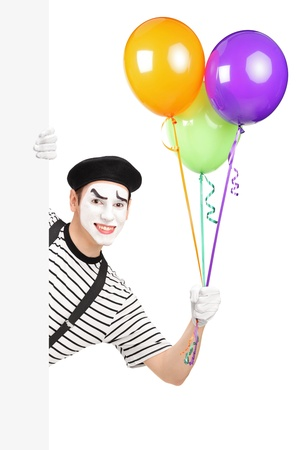 pantomima: Mime artista sostiene un manojo de globos y asomándose desde un panel blanco, aislado en fondo blanco