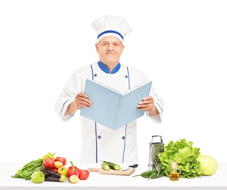 A mature chef reading a cookbook during a preparation of fresh salad isolated on white background photo