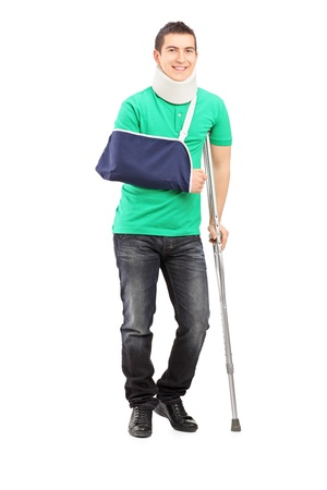 crutch: Full length portrait of a smiling male with broken arm and crutch isolated on white background