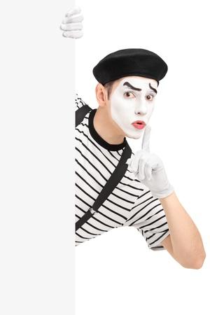 pantomima: Hombre mimo con un panel en blanco y gesticula silencio con un dedo en la boca, aislado en fondo blanco Foto de archivo