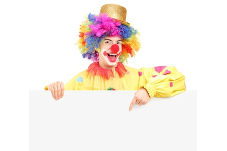 A happy male clown pointing on a blank panel isolated on white background photo