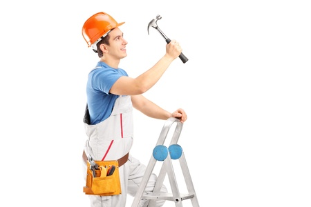 A repairman on a ladder working with a hammer isolated on white background photo