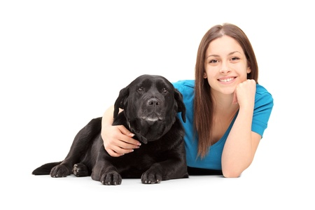 animal woman: A young female lying and posing with a black dog isolated on white background