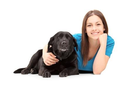 mujer perro: Una joven mujer acostada y posando con un perro negro sobre fondo blanco Foto de archivo