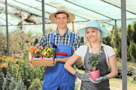 Female and male gardeners holding flower pots and posing in a hothouse photo