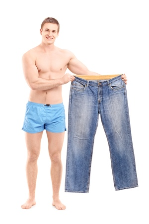 Full length portrait of  a fit muscular man holding a pair of jeans, isolated on white background photo