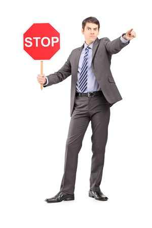 Full length portrait of a man in suit holding a stop sign, isolated on white background photo