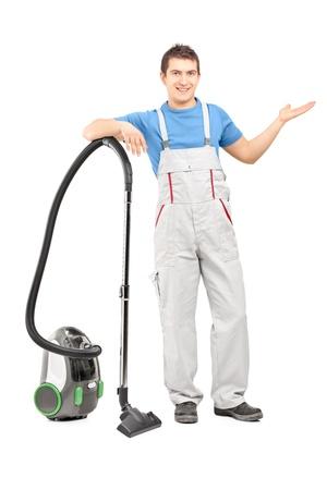 empleada domestica: Retrato de cuerpo entero de un empleado del servicio de limpieza que presenta con una aspiradora, aislado en fondo blanco