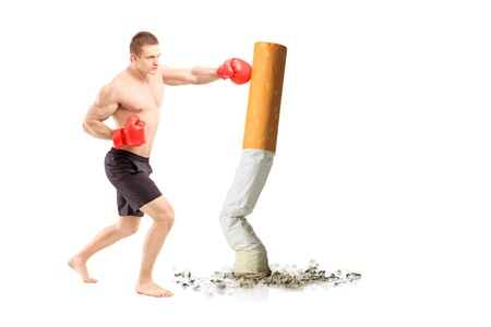 male athlete: Full length portrait of a male athlete with boxing gloves, punching a cigarette against white background
