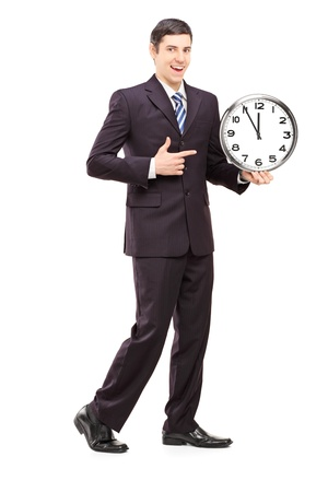 punctual: Full length portrait of a youn man in suit pointing on a clock, isolated on white background