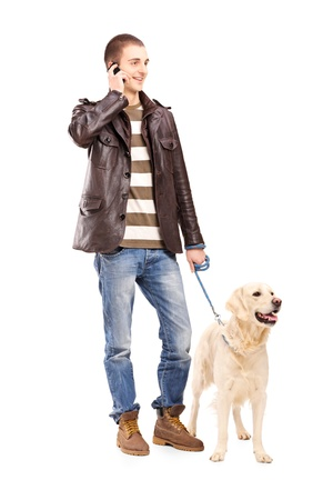 Full length portrait of a young man walking a dog and talking on a mobile phone, isolated on white background photo