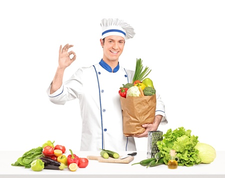 Male chef holding a paper bag full of healthy vegetable ingridients next a table, isolated on white background photo