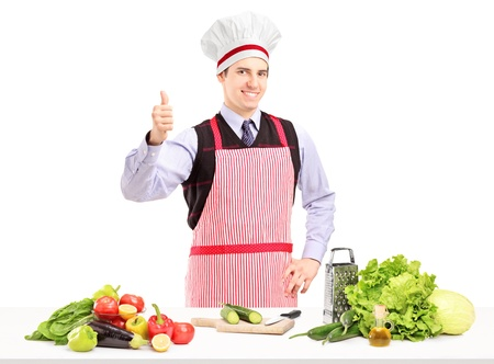 Man with apron posing with vegetables and giving a thumb up, isolated on white background photo