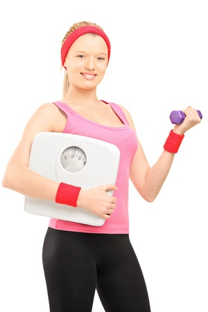 Young female holding a dumbbell and a weigth scale, isolated on white background photo
