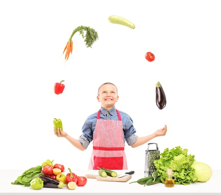 A boy with apron juggling with vegetables while preparing salad isolated on white background photo