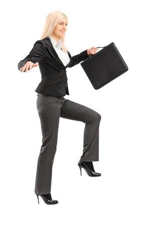 Full length portrait of a businesswoman holding a briefcase and trying to keep balance, isolated on white background photo