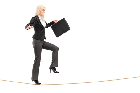 Full length portrait of a businesswoman with briefcase, trying to keep balance while walking on a rope, isolated on white background photo