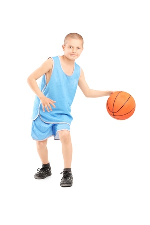 sport kids: Full length portrait of a child playing with a basketball isolated against white background