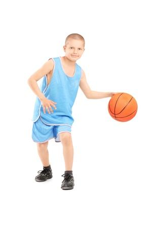Volledige lengte portret van een kind spelen met een basketbal geïsoleerd tegen een witte achtergrond